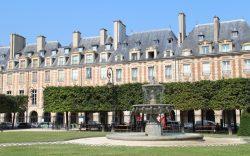 Place des Vosges (ancienne Place Royale) vue du square Louis XIII et de la fontaine au centre.